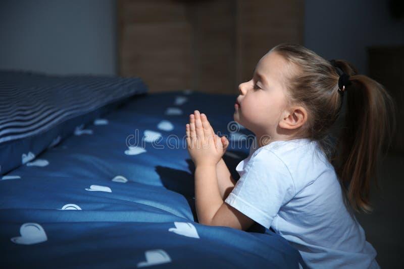 Niña que dice rezo de la hora de acostarse cerca de cama en sitio imagen de archivo libre de regalías