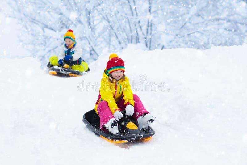 Niña que disfruta de un paseo del trineo El sledding del niño Niño del niño que monta un trineo Juego de niños al aire libre en n fotografía de archivo libre de regalías