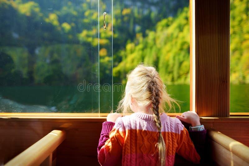 Niña que disfruta de una vista de aguas de color verde oscuro de Konigssee mientras que viaja en barco eléctrico imagen de archivo libre de regalías