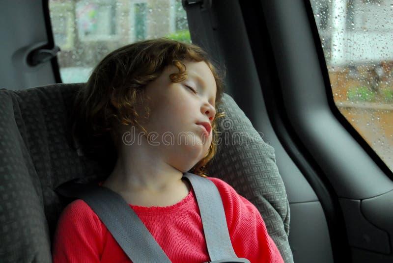 Niña que duerme en asiento de coche imagenes de archivo