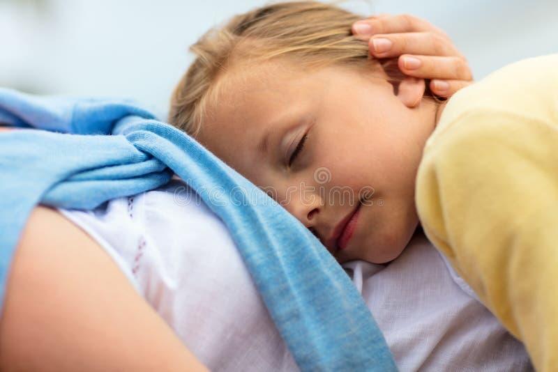 Niña que duerme en revestimiento de la madre fotos de archivo