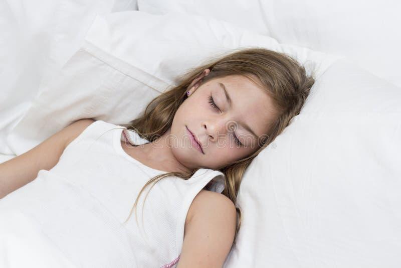 Niña que duerme en su cama fotografía de archivo libre de regalías