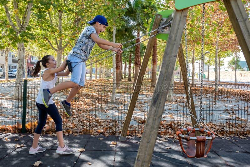 Niña que empuja a un niño en el oscilación en un parque imágenes de archivo libres de regalías