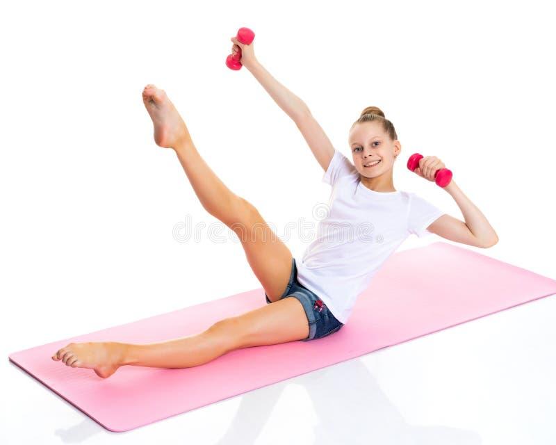 Niña que hace ejercicios con pesas de gimnasia foto de archivo libre de regalías