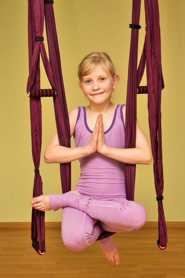 Niña que hace los ejercicios aéreos de la yoga, interiores imagenes de archivo