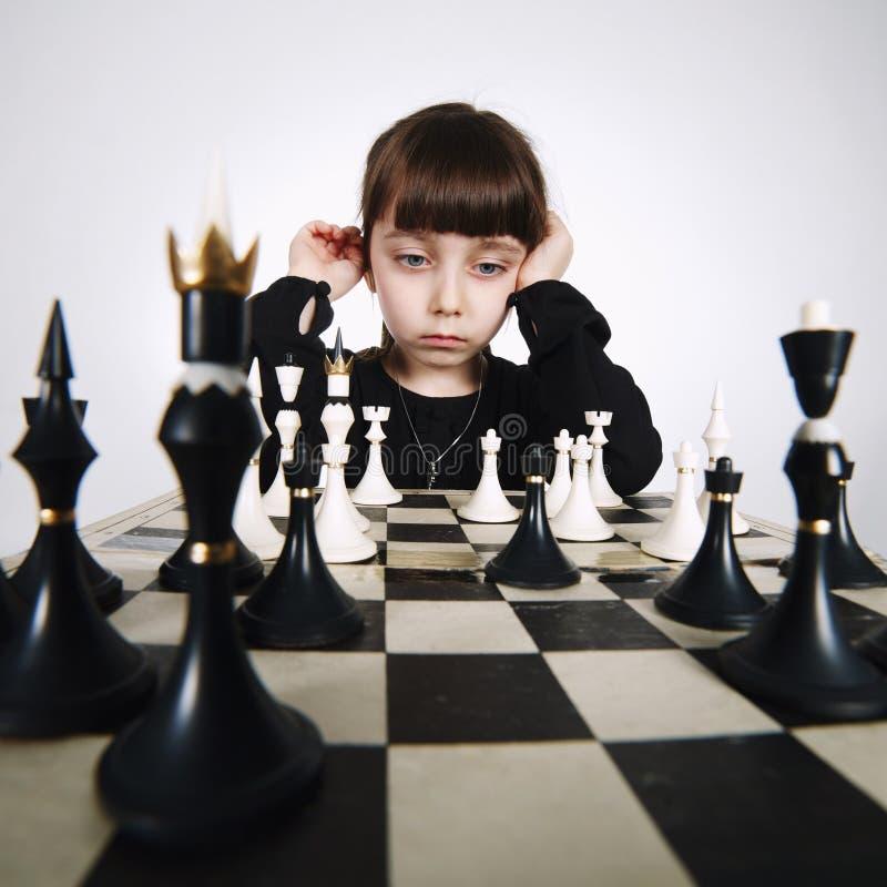 Niña que juega a ajedrez en blanco fotos de archivo