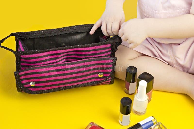 Niña que juega con el bolso y el esmalte de uñas cosméticos, fondo amarillo, cosméticos fotos de archivo