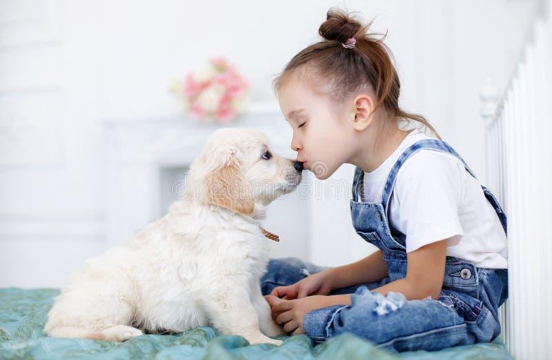 Niña que juega con el perro perdiguero de los perritos fotografía de archivo libre de regalías
