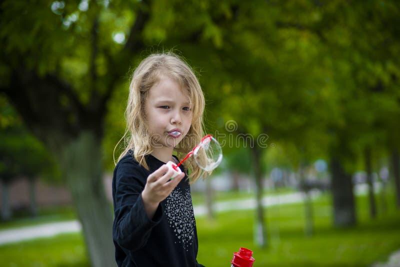 Niña que juega con las burbujas de jabón imagenes de archivo