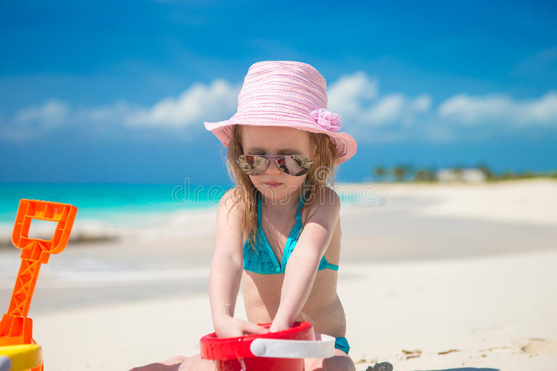 Niña que juega con los juguetes de la playa durante foto de archivo
