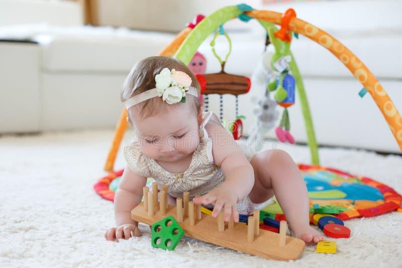 Niña que juega con los juguetes en casa en el piso imagen de archivo