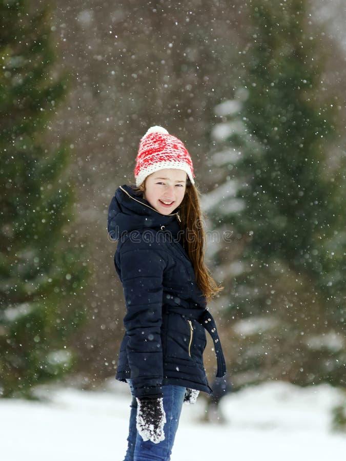 Niña que juega con nieve mientras que es snowflurry foto de archivo