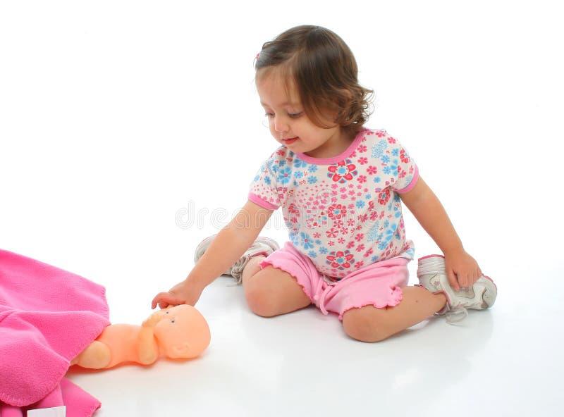 Niña que juega con su bebé foto de archivo