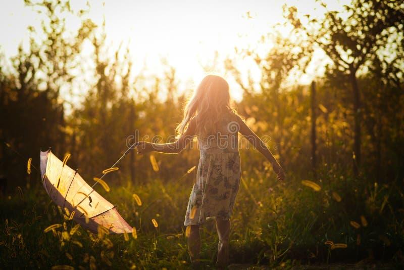 Niña que juega con su paraguas en el parque en la puesta del sol imagenes de archivo