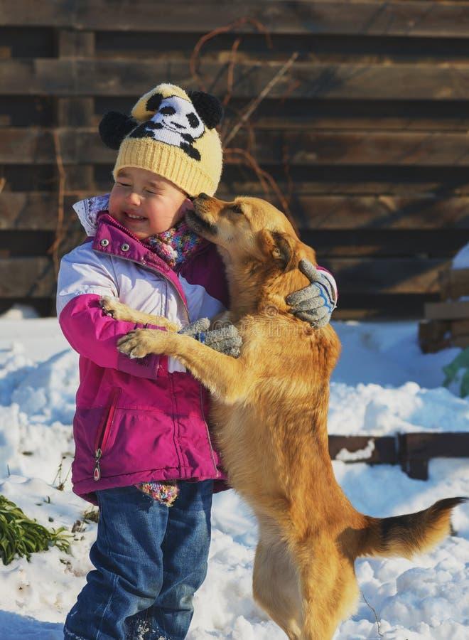 Niña que juega con un perro mestizo en la nieve fotos de archivo