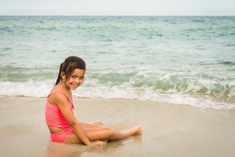 Niña que juega con una estrella de mar en la playa imagen de archivo