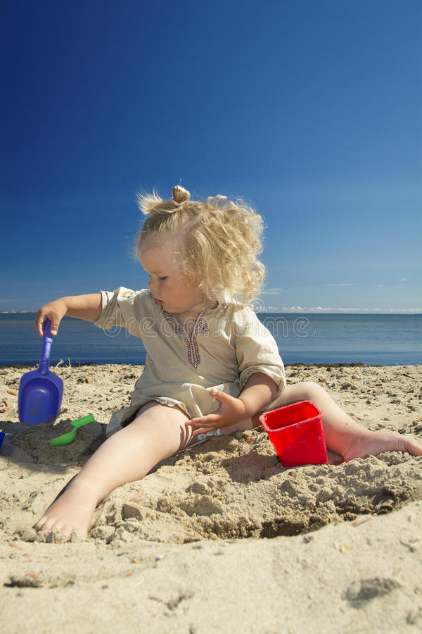 Niña que juega en la arena en la playa por el mar imágenes de archivo libres de regalías