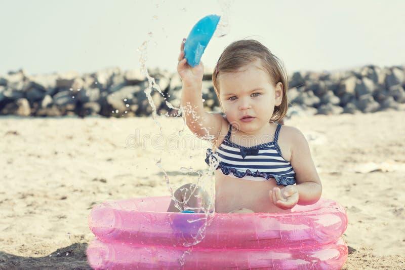 Niña que juega en la playa, cerca del mar imagen de archivo