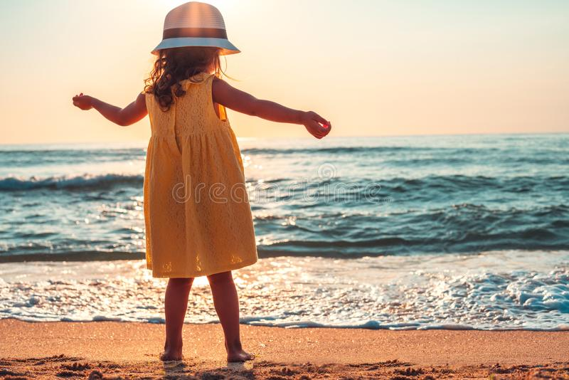 Niña que juega en la playa Salida del sol sobre el mar imagenes de archivo