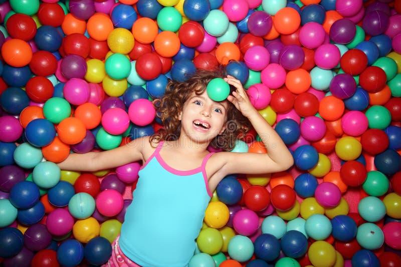Niña que juega en patio colorido de las bolas fotos de archivo libres de regalías
