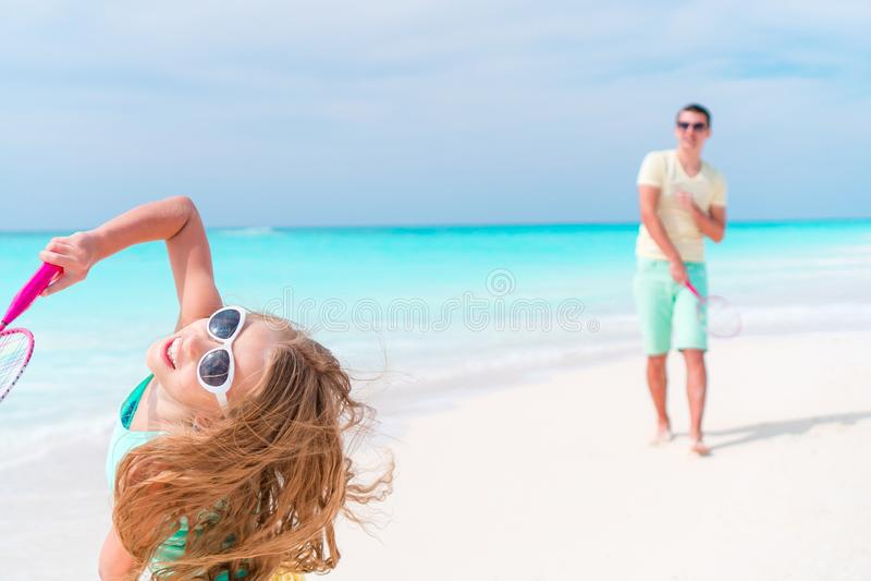 Niña que juega a tenis de la playa el vacaciones con el padre joven foto de archivo