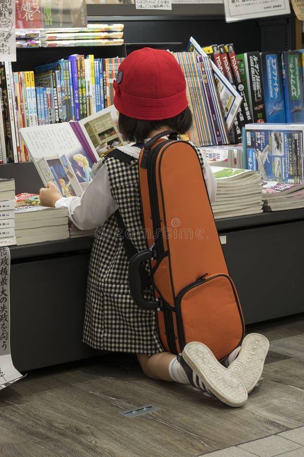 Niña que lee un libro en una librería japonesa con una caja del violín en ella detrás imagen de archivo