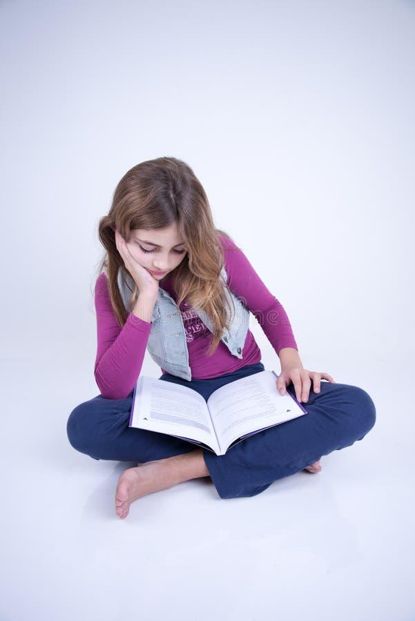 Niña que lee un libro que se sienta en el piso fotos de archivo