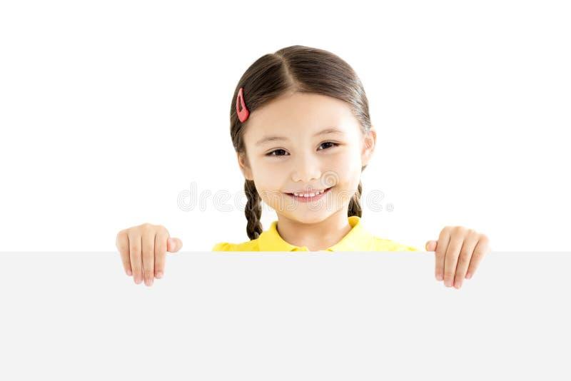 Niña que lleva a cabo al tablero blanco en blanco imagen de archivo libre de regalías