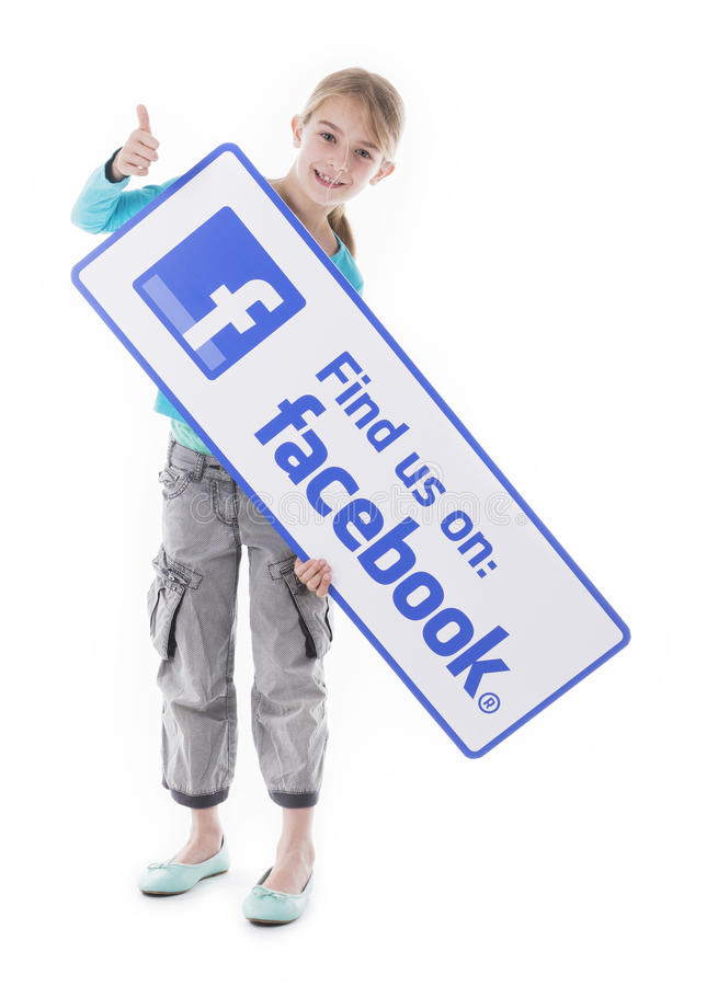 Niña que lleva a cabo la muestra de Facebook foto de archivo libre de regalías