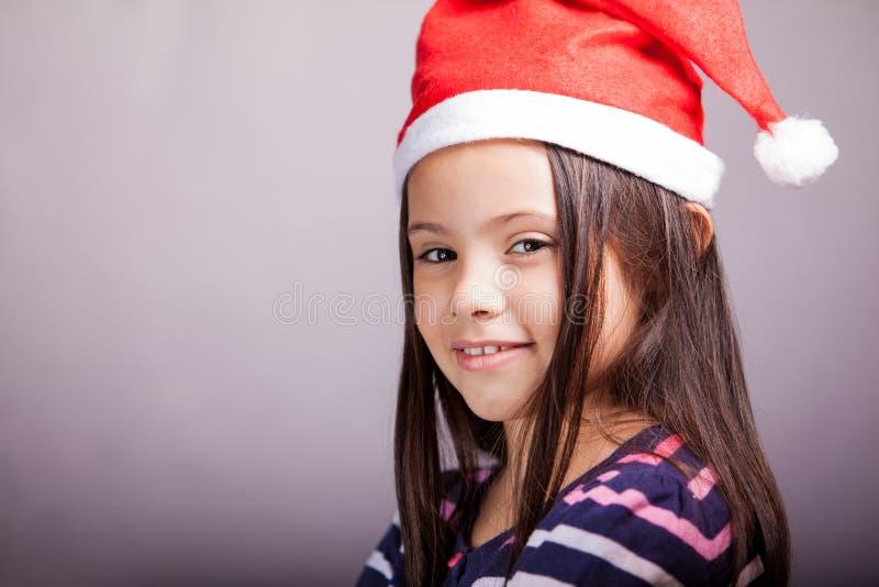 Niña que lleva el sombrero de Papá Noel imagen de archivo libre de regalías