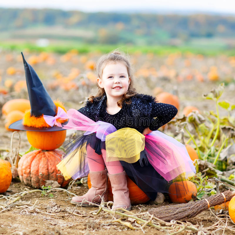 Niña que lleva el traje de la bruja de Halloween en remiendo de la calabaza foto de archivo libre de regalías