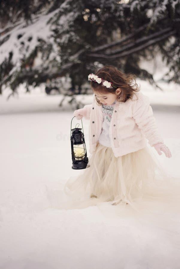 Niña que lleva una capa beige y un vestido largo, mirando la lámpara con la vela que se coloca entre las ramas, cubiertas con nie fotos de archivo libres de regalías
