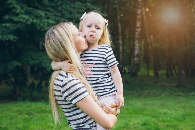 Niña que llora en los brazos de su madre fotografía de archivo libre de regalías