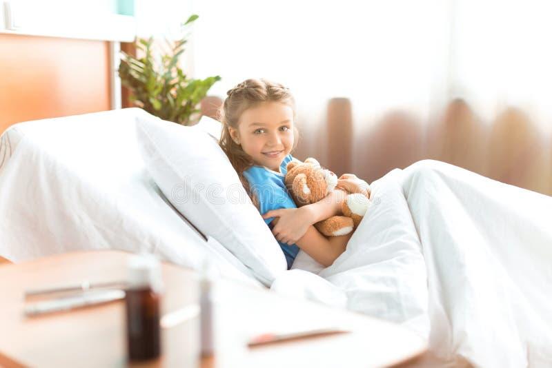 Niña que miente en cama de hospital con el oso de peluche y que sonríe en la cámara fotos de archivo