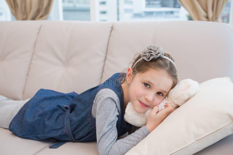Niña que miente en el sofá con el peluche foto de archivo libre de regalías