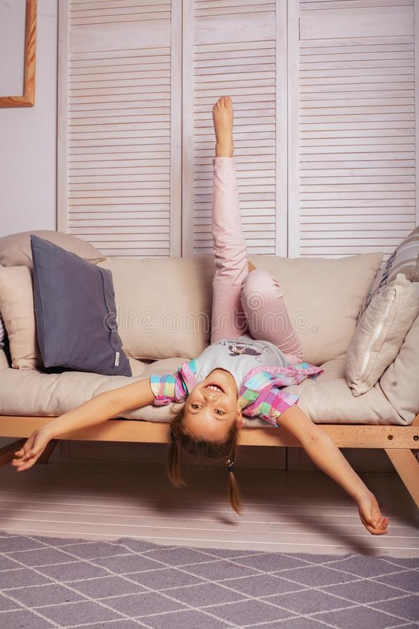 Niña que miente en el sofá El concepto de niñez y de lif fotografía de archivo