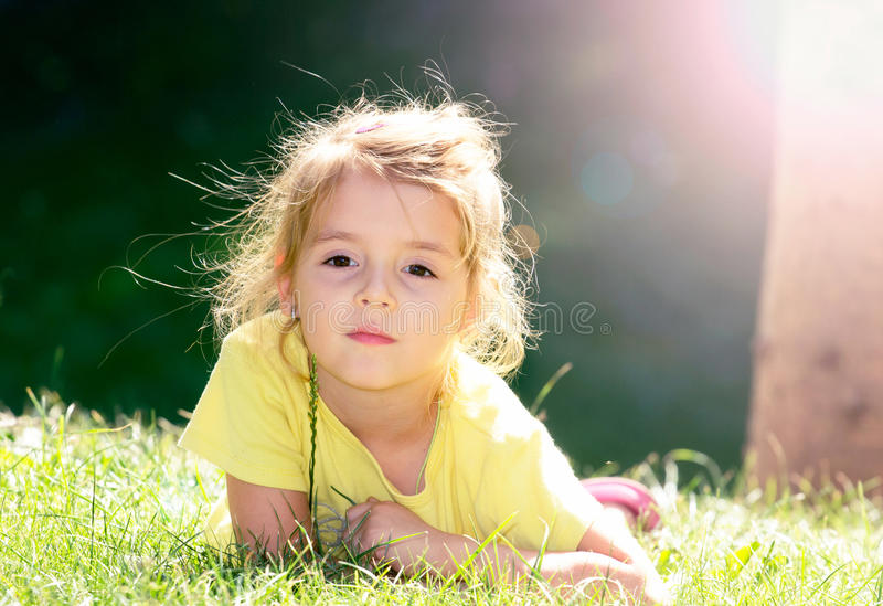 Niña que miente en la hierba verde Cara al aire libre del primer del niño fotos de archivo