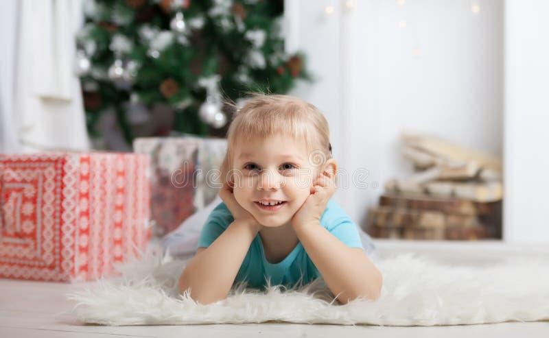 Niña que miente en piso cerca del árbol de navidad foto de archivo libre de regalías