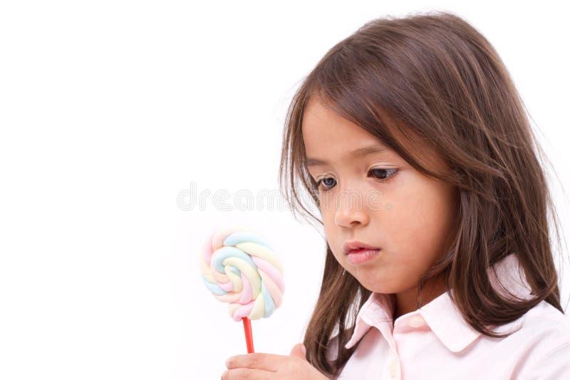 Niña que mira el caramelo dulce de la melcocha imagenes de archivo