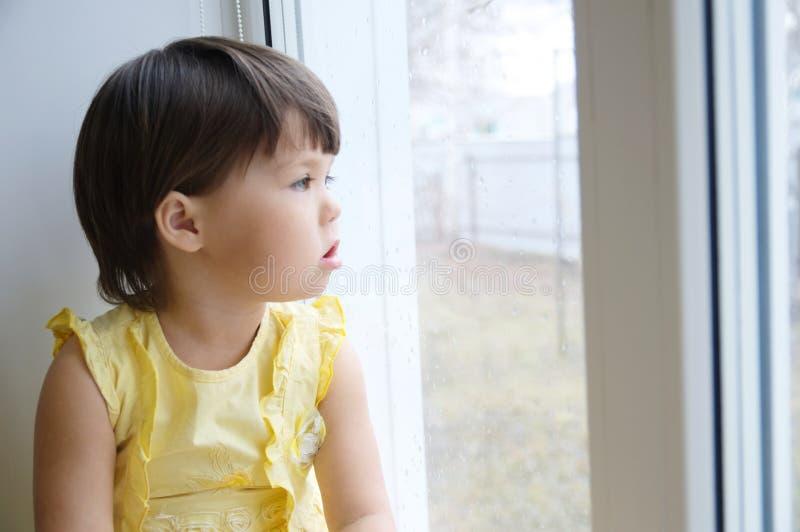 Niña que mira hacia fuera el anhelo de la ventana para un poco de sol niño que se sienta a casa en el día lluvioso foto de archivo