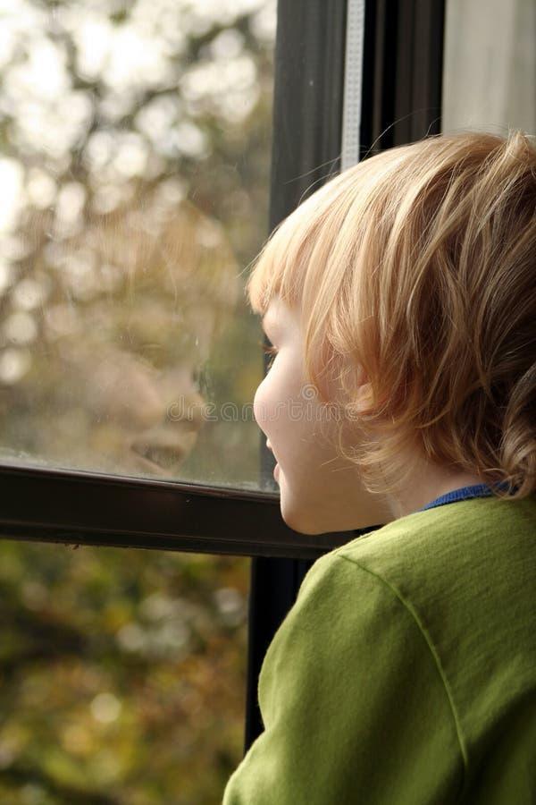 Niña que mira hacia fuera la ventana foto de archivo libre de regalías