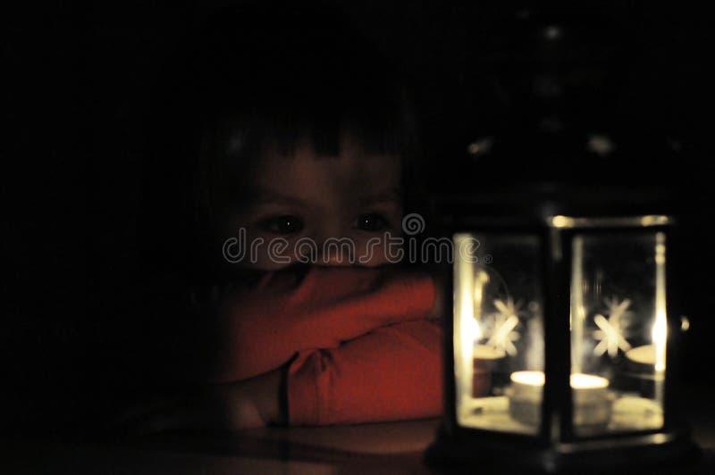 Niña que mira la luz de la vela en linterna fotos de archivo