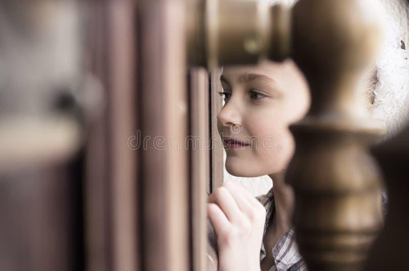 Niña que mira la ventana de la puerta del tiro fotos de archivo