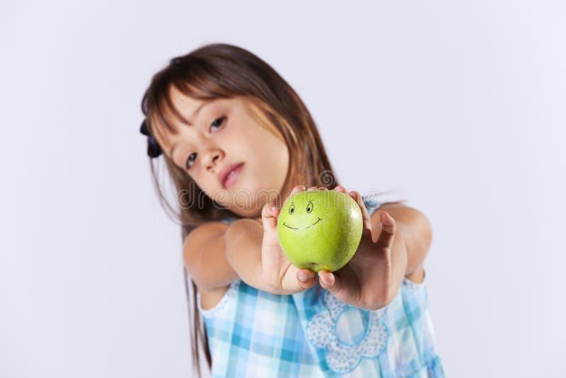 Niña que muestra una manzana verde fotografía de archivo
