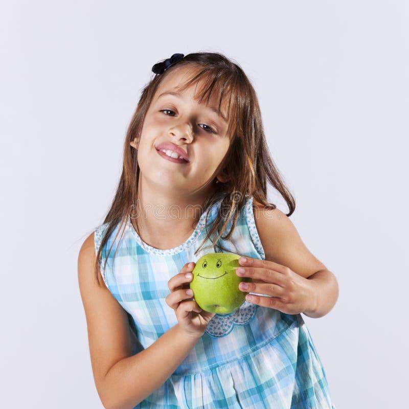 Niña que muestra una manzana verde imagen de archivo