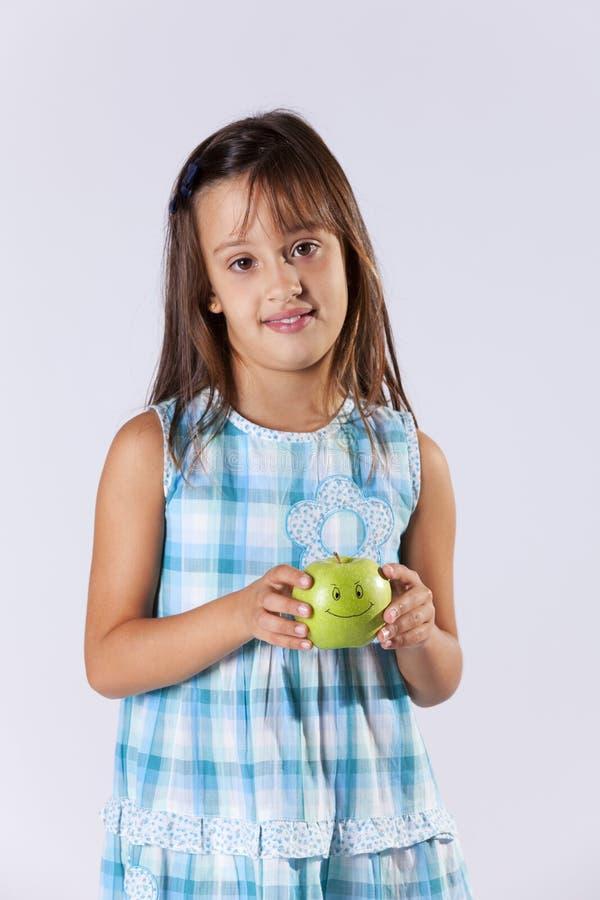 Niña que muestra una manzana verde foto de archivo