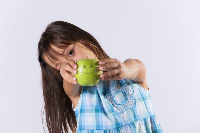 Niña que muestra una manzana verde imágenes de archivo libres de regalías