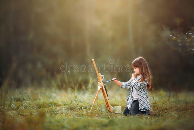 Niña que pinta al aire libre foto de archivo