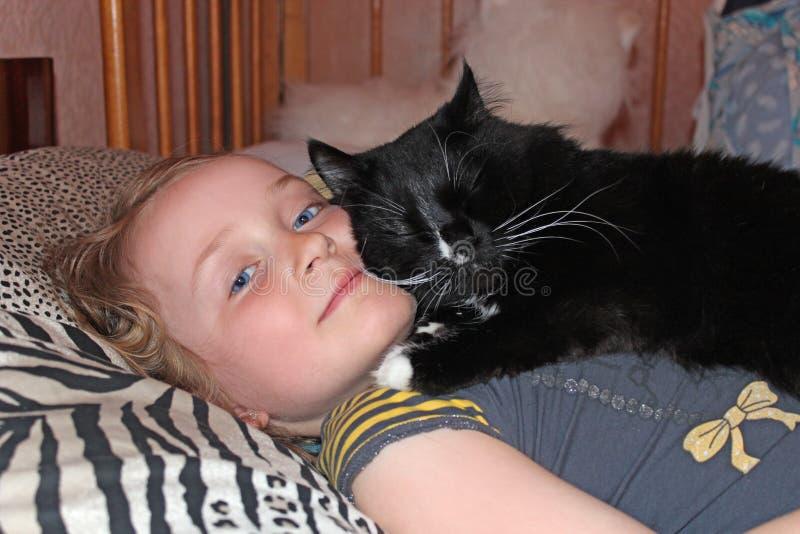 Niña que pone en cama así como su gato Así como su animal doméstico fotos de archivo libres de regalías