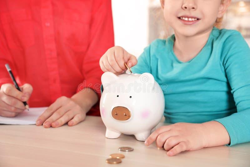 Niña que pone la moneda en la hucha y su madre en la tabla Dinero del ahorro fotos de archivo